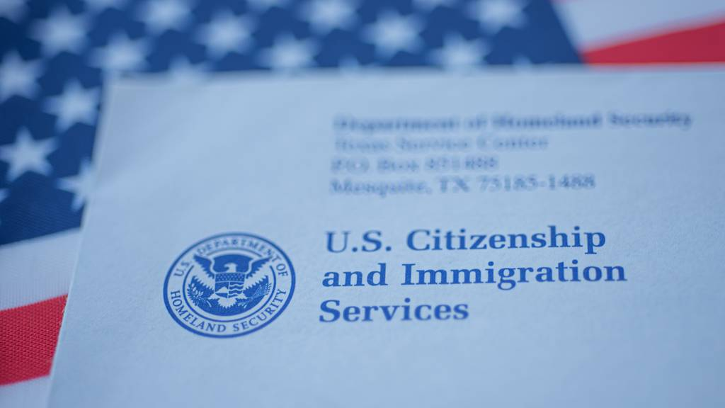 A U.S. Citizenship and Immigration Services envelope rests on an American flag.