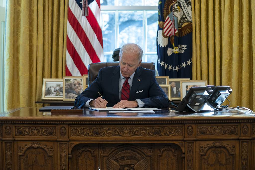 In this Jan. 28, 2021, file photo President Joe Biden signs a series of executive orders on health care, in the Oval Office of the White House in Washington.