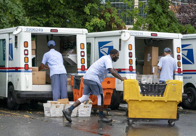 In this July 31, 2020, file photo, letter carriers load mail trucks for deliveries at a U.S. Postal Service facility in McLean, Va.