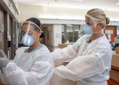 Ensign Kaitlyn Leibing, right, helps Hospitalman Angela Mello don personal protective equipment (PPE) before entering a COVID-19-positive, non-critical patient's room at Naval Medical Center San Diego on Aug. 4, 2020.