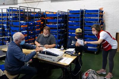 Chester County, Pa., election workers process mail-in and absentee ballots for the 2020 general election in the United States at West Chester University, Wednesday, Nov. 4, 2020, in West Chester, Pa